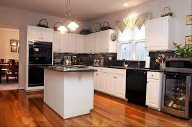 GREG DOHLER/The Gazette Black appliances contrast nicely with white  cabinetry in the kitchen.