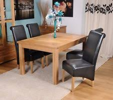 extending solid oak dining table and four black bonded leather chairs 120 165cm