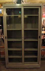 and glass sliding door cabinet in its original metal gray color in good condition with scratches along one side lacquered black wood block pulls