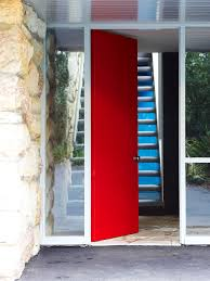 red front door opening to entrance lobby at bottom of stairs at rose seidler house