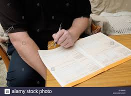 man filling in an application form to claim for benefits stock man filling in an application form to claim for benefits
