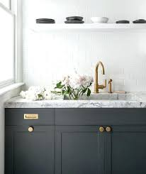 white marble countertops dark gray kitchen cabinets accented with aged brass knobs vintage brass inset pulls and a honed gray and white marble completed