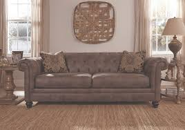 on tufted elegant worn gray leather look sofa with morrocan designed pillows with brown wood wall