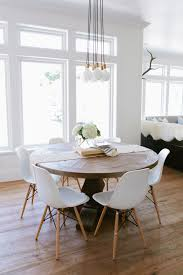 bulb ceiling light above round dining table for exterior dining room with modern chairs decoration and white wall paint color also using glass window design
