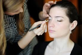 young beautiful woman applying wedding make up by make up artist