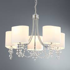 the fitting is adorned with delicate crystal beads and chains that hang gracefully below the shades and the five lights brighten the room beautifully
