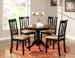 elegant black round pedestal kitchen table and chairs set featuring decorative vase and round scroll kitchen