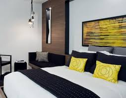 couple bedroom with black and white tone popped up with yellow pillows and painting for bedroom decorating ideas