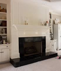 i painted our damaged black tiles on our fireplace to look like marble it