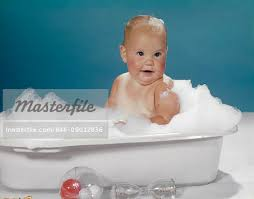 1950s 1960s clean happy baby sitting in plastic bath tub basin full of soap suds stock photo