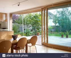 large sliding patio doors: stock photo wooden dining table and chairs in front of large sliding glass doors residential house lloyd close uk