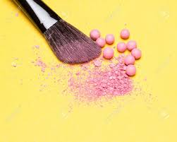 close up of makeup brush with crushed and whole shimmer blush pink color on