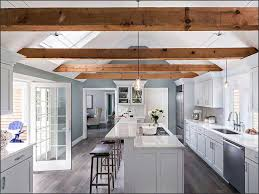 house in cape cod with utilizing exposed beams with pendant lights used over the breakfast bar
