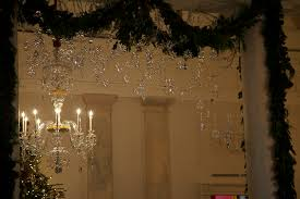 snowflakes garland and a chandelier decorate tthe white house for