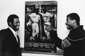 ken griffey jr road to cooperstown the news tribune and the ken griffey jr right and dad ken griffey kid around next to a poster featuring both of them in their teams uniforms 8 1989 at riverfront stadium