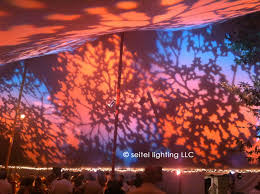 rosy amber pink lavender and blue leaf patterns projected onto the wedding tent using gobos and split gels in theatrical lekos mounted to the tent poles