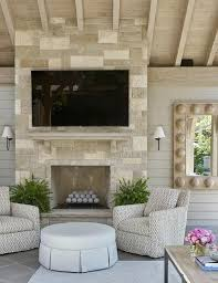 cream stone outdoor fireplace with flat panel television
