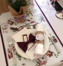Floral table runner with lace edges over plain purple runner. Two ...