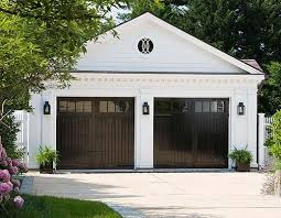 high gloss black garage doors act like a mirrored surface for a home s driveway and surrounding greenery matching sconces reinforce the stark color and