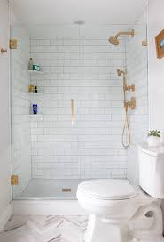 walk in shower design with subway tiles and brass accents
