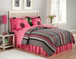 pink gray fl and stripped pattern bedding set placed on the white wooden bed