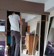 man unfastening the top of a mirrored wardrobe door