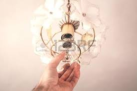 changing light bulbs in chandelier stock photo a