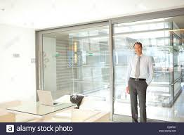 glass door office. Businessman Leaning Against Glass Wall In Office - Stock Image Door
