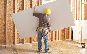 a man holding a large sheet of drywall in an unfinished space