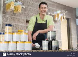 s clerk standing at the counter of a paint shop and smiling s clerk standing at the counter of a paint shop and smiling