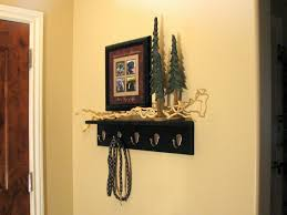 furniture black wooden wall mounted coat rack with shelf and five hook on cream wall