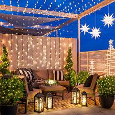 outdoor space with string lights attached to beams and a wall with lighted stars