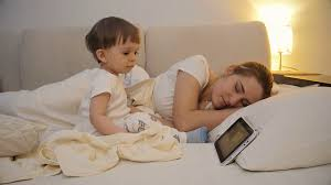 4k fooe of cute baby boy watching cartoons on digital tablet while mother sleeping next to