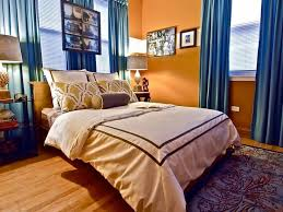 eclectic orange bedroom with bold blue curtains