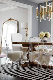 the dining table is surrounded by fur covered lucite chairs though they look absolutely chic the chairs have a functional purpose