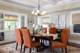 beautiful orange chairs bring color to the traditional dining room design and interior design