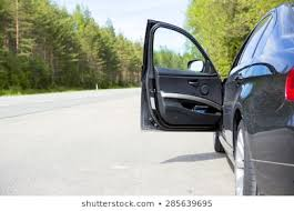 a black vehicle with an open door in side of the road image taken during
