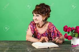 old lady or grandmother old woman reading book with gles at flowers writer and