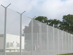 barbed wire fence prison. With Barbed Wire Topping, A White PVC Coated Prison Security Fence Is Installed At