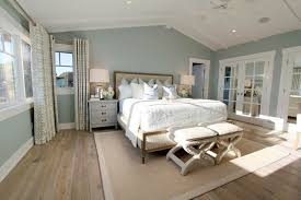 steely light blue bedroom walls wide plank rustic wood floors patterned curtains
