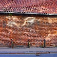 street scene with old brick wall with