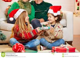 Siblings Giving Gifts To Each Other At Christmas Stock Photo Giving Gifts On Christmas
