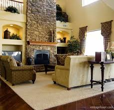 this living room takes a risk with patterns the dark stone fireplace offers a statement while the dark floors makes the room appear smaller than it is
