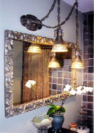 bathroom with framed ornate mirror and swag lamps
