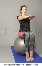 women sitting on a gym ball holding her arms straight csp55356641