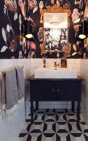 an antique dresser was converted into a bathroom vanity i love the eclectic wallpaper by