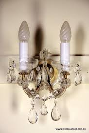 two crystal wall sconces mid 20th century the two branch sconces with curvaceous ribbed arms supporting cut crystal pans and candle style electric candles
