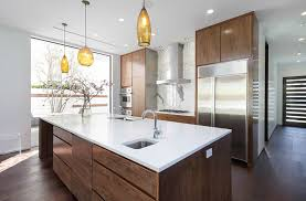 modern kitchen with white quartz countertops and pendant lights