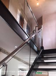 A black oak staircase with steel rails, glass balustrade and glass risers.