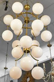 18 white murano glass globes cascade down a mid century modern style brass structure on